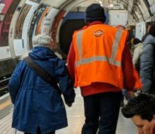 A station worker assists a passenger